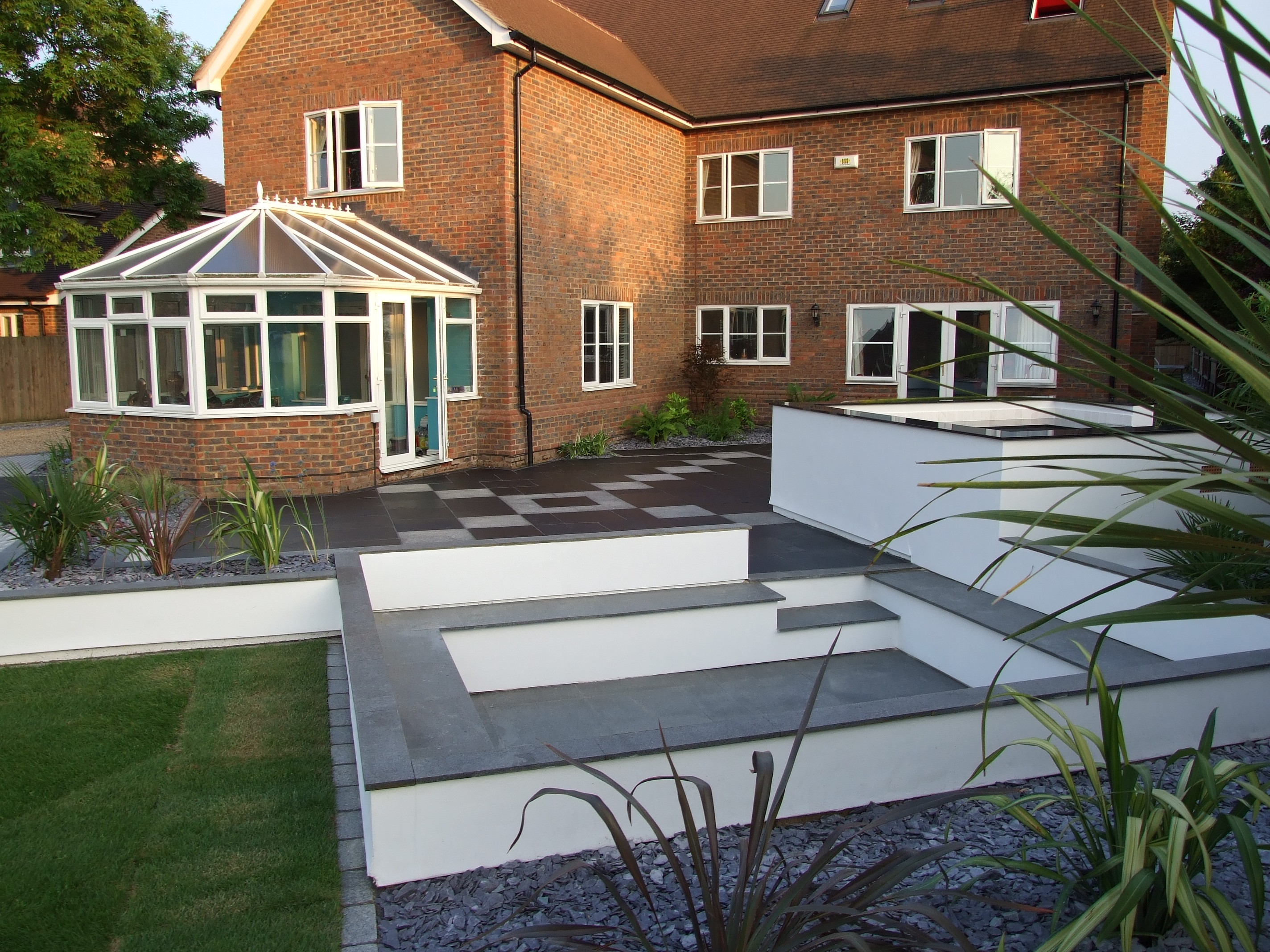 image of garden makeovers showing granite fire pit, outdoor kitchen and stunning granite and limestone paving